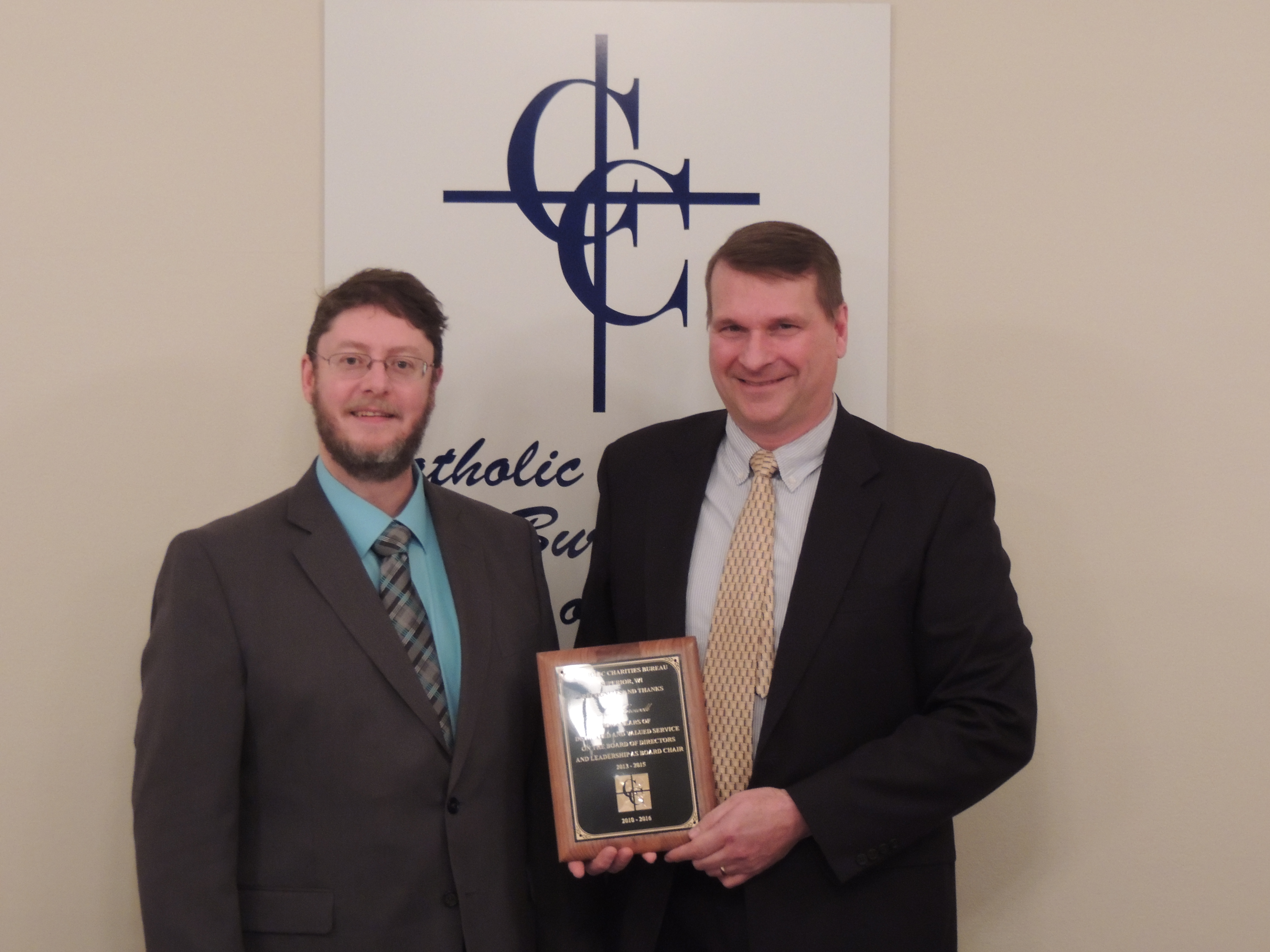 Kyle Torvinen (left), Chair of the Catholic Charities Bureau Board of Directors presents Matt Crowell (Right) with a plaque for his service on the Board